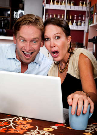 pornography: Attractive couple in a coffee house with laptop computer