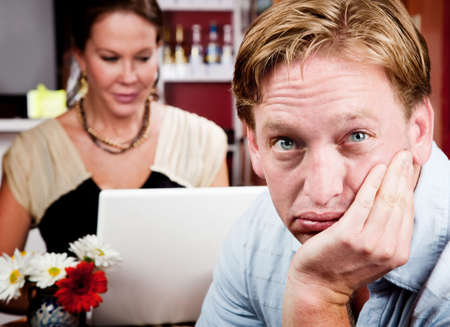 preoccupied: Bored man with woman on laptop computer in coffee house Stock Photo