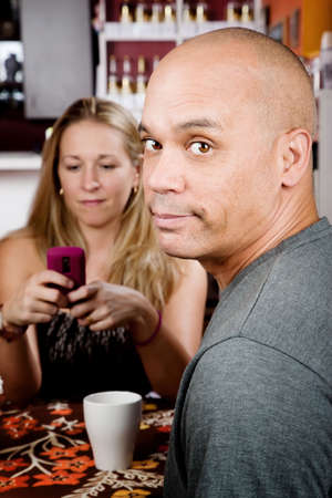 bored man: Bored man with woman on cell phone in coffee house Stock Photo