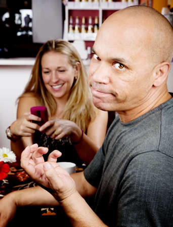 Bored man with woman on cell phone in coffee house photo