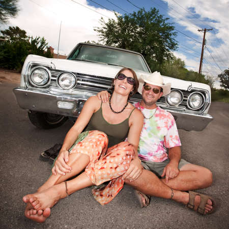 Happy Adult Couple with Vintage White Car photo