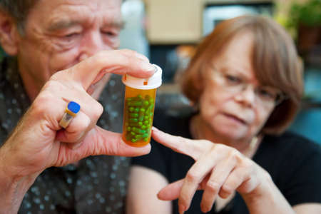 senile: Senior couple at home with prescription bottle