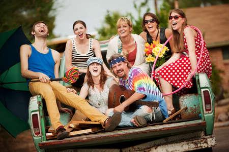 mujer hippie: Groovy Grupo en la parte trasera del cami�n que r�e Foto de archivo