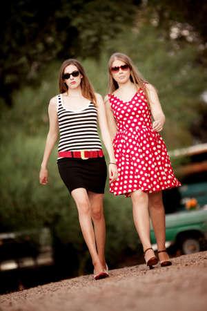 Fashion Girls Walking on Dirt Road Towards Camera photo