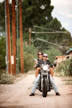 Man and Woman riding motorcyle on dirt road photo