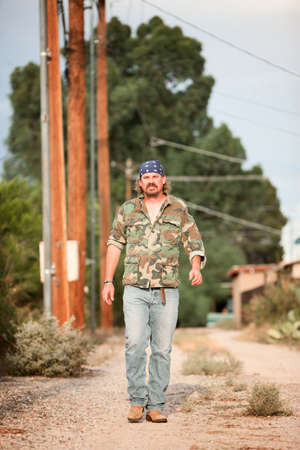 Rugged man in camoflauge walking on dirt road Stock Photo - 5619545