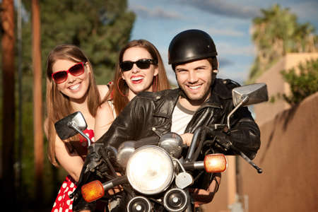 Three young adults posing on vintage motorcycle
