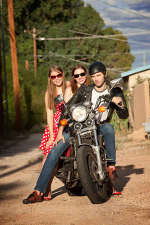 Three young adults posing on vintage motorcycle photo