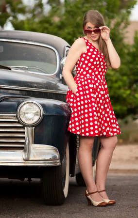 dirty car: Young girl in red polka dot dress with vinatge car