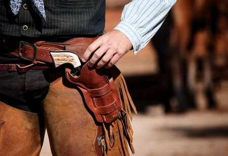 Closeup of cowboy with chaps, gun and leather belt