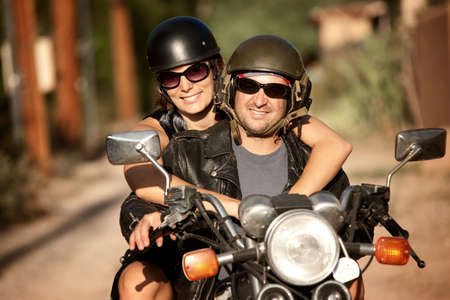 Man and Woman riding on vintage motorcyle photo