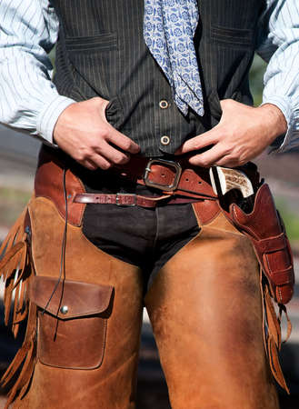 Closeup of cowboy with chaps, guns and leather belt photo