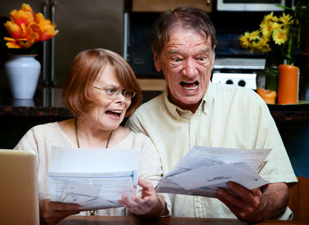 Senior couple at home reacting to many bills photo