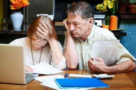 chequera: Senior couple en casa reaccionar a muchos proyectos de ley