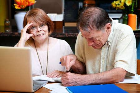 reacting: Senior couple at home reacting to many bills