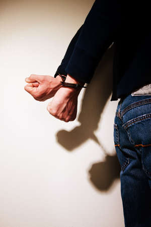 cuffs: Young man with hands cuffed behind his back