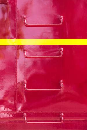 rungs: Pelda�os de la escalera de metal en el lado del vag�n de cola del tren rojo