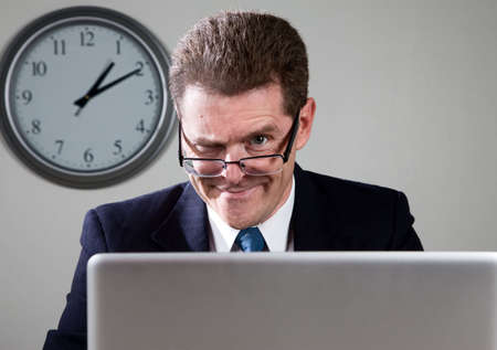 devious: Crazy businessman working late at desk on laptop computer Stock Photo