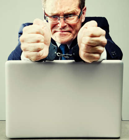 cuffs: Businessman in handcuffs at desk with laptop computer Stock Photo