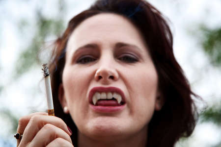 Female vampire smoking a cigarette and baring her teeth Stock Photo - 5738284