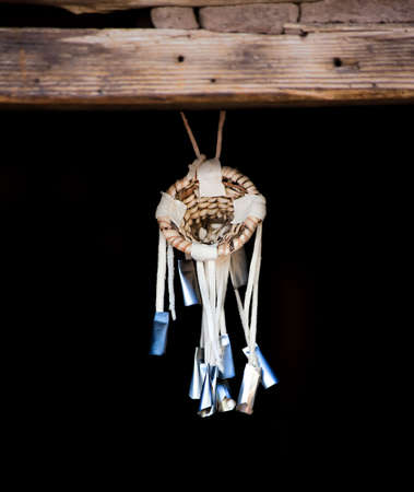 portent: Native American Dream Catcher Suspended from Wooden Beam