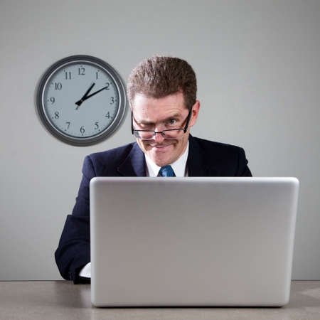 Crazy businessman working late at desk on laptop computer Фото со стока