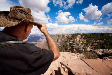 Male hiker looking over the ridge of the Grand Canyon photo