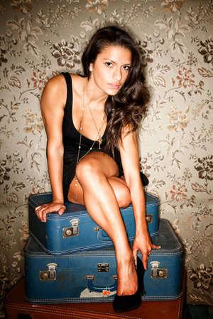 Woman sitting on vintage suitcases adjusting her high heel shoe photo