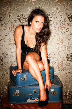 mexican dress: Woman sitting on vintage suitcases adjusting her high heel shoe Stock Photo