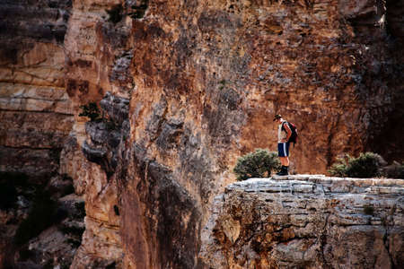 Man standing on a rocky outcropping in the Grand Canyon photo