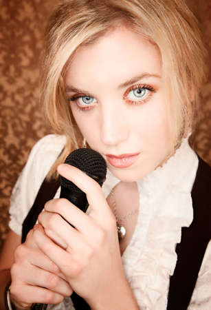 Pretty blonde woman with a black microphone photo