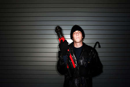 Young burglar in leather jacket with crowbar and bolt cutter photo
