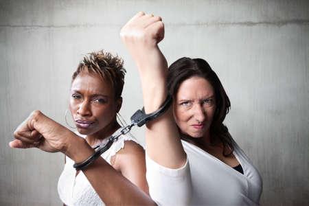 desprecio: Dos mujeres enojado joind por un par de esposas Foto de archivo