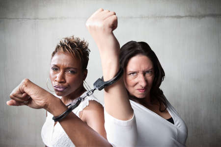 Two angry women joind by a pair of handcuffs photo