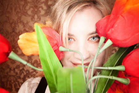 fake smile: Pretty young blonde woman with colorful plastic tulips Stock Photo