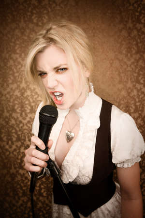 sneer: Pretty young female blonde singer or comedian with microphone Stock Photo