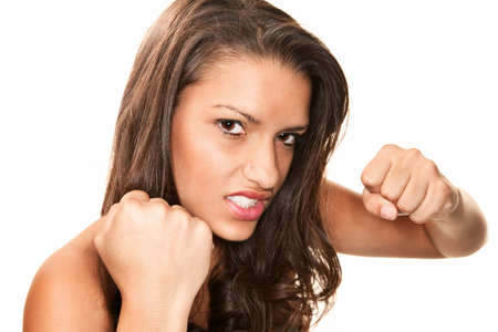 Pretty young brunette Hispanic woman throwing a punch photo