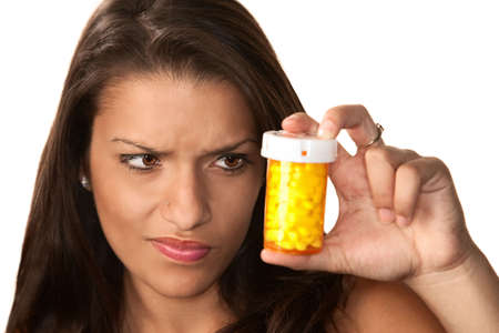 Pretty Hispanic woman reading label on prescription medication Stock Photo - 5927130