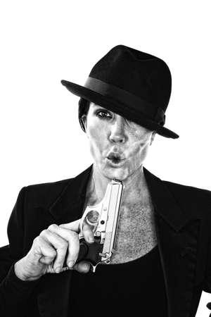 assasin: Woman blowing on the barrel end of a smoking gun