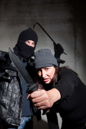 an assailant: Male and female criminals wielding dangerous weapons