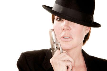 assasin: Beautiful woman holding small handgun against her cheek