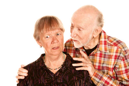 unease: Handsome senior man sharing information with his concerned wife