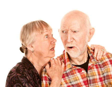 unease: Senior woman sharing important information with skeptical man Stock Photo