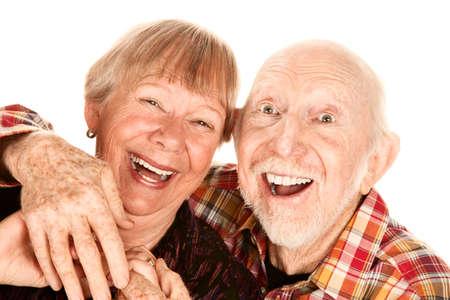 broadly: Happy senior couple on white background laughing broadly