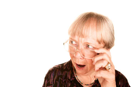 appalled: Shocked senior woman looking sideways over the top of her glasses