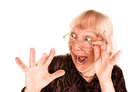 sideways: Shocked senior woman looking sideways over the top of her glasses