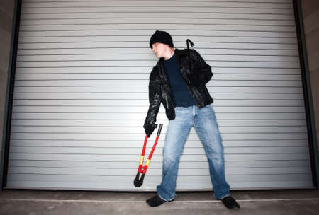 Burglar with tools in front of industrial door