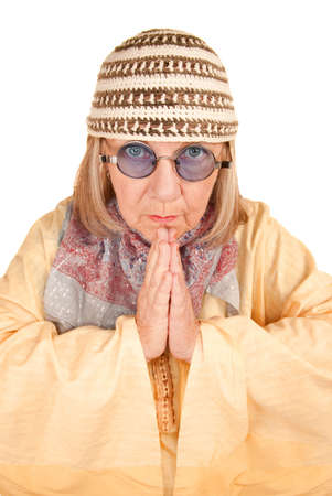 Crazy new age woman with hands together in a yellow robe photo