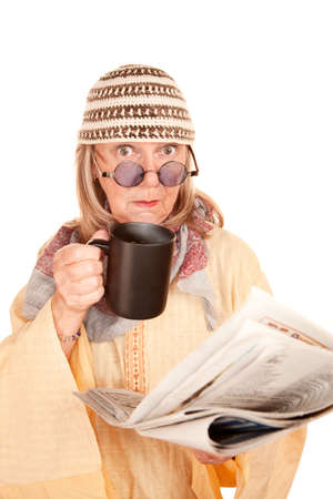 new age: Crazy new age woman in a yellow robe with coffee cup and newspaper Stock Photo