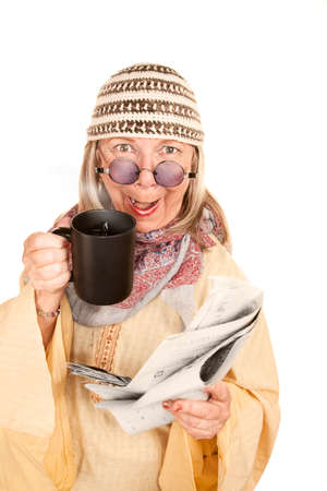 newage: Crazy New-Age Woman in Yellow Robe with Coffee and Newspaper Stock Photo